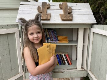 a young girl stands in front of a little library with her hands full of free art packets to distribute to her community