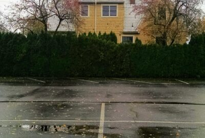 bottom half of the photograph is of a parking lot filled with rain puddles while the top half of the photograph is a yellow house