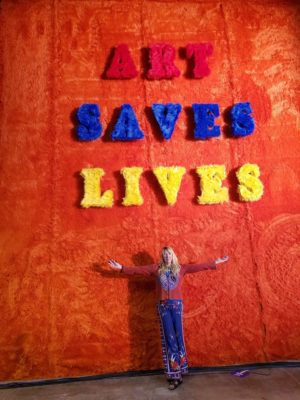 Lisa Rasmussen standing in front of an artwork that says Art Saves Lives.